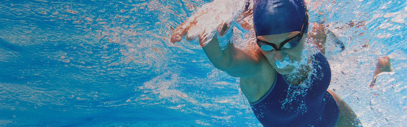 Woman swimming underwater wearing goggles and a swim cap